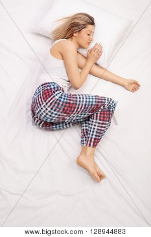 Vertical shot of a young woman in checkered pajamas sleeping on a comfortable bed