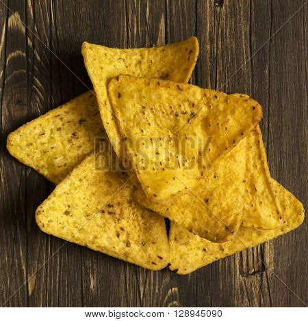 Pile of nachos over wooden background. Top view