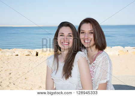 pretty young friends sitting by the sea smiling