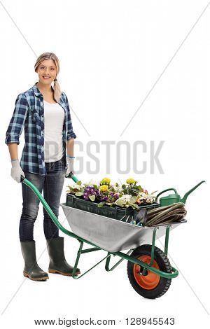 Full length portrait of a young woman pushing a wheelbarrow with gardening equipment isolated on white background