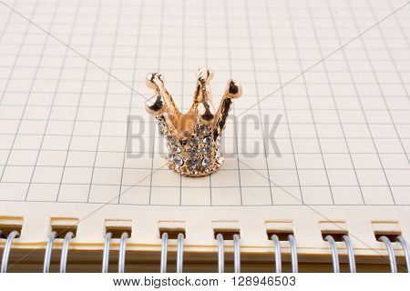 Crown with a notebook on a white background