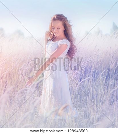 Beauty Girl Outdoors enjoying nature. Beautiful Romantic Teenage Model girl with perfect long curly hair, in white dress standing on the Spring Field, Raising hands in Sun Light, pastel colors