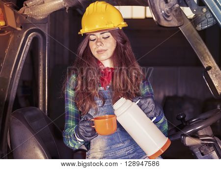 Portrait Of A Worker Young Girl On Coffee Break On A Forklift