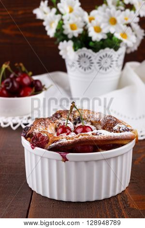 French clafoutis with cherry in ceramic ramekins on rustic wooden table