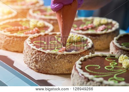 Cakes with bright floral ornament. Hand with tool decorating cake. Fresh delicious cakes at factory. Creating tasty things.