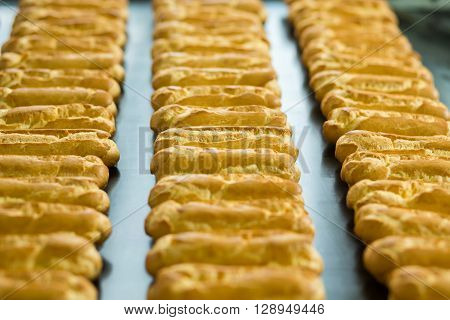 Long rows of eclair shells. Eclairs on wide conveyor belt. Each one has perfect shape. Company's standards of production.