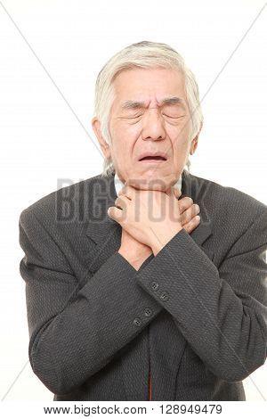 portrait of senior Japanese businessman having throat pain