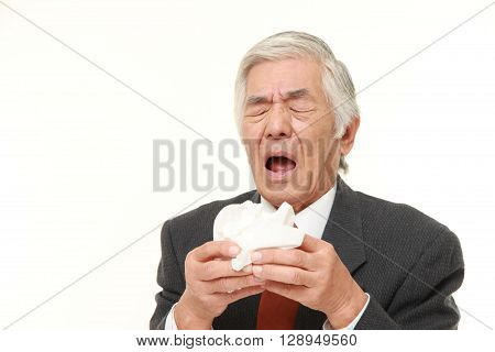 senior Japanese businessman with an allergy sneezing into tissue