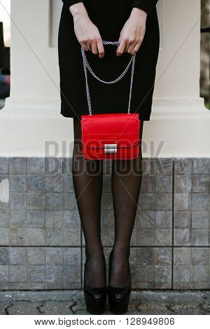 lifestyle portrait of young stylish woman goes in the city with a red trendy bag. On the girl shoulder clutch bag, wearing a black dress, wearing a headband with precious stones. Earrings, jewelry