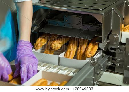 Boxes of eclairs on conveyor. Hands working with baked pastry. Machine puts eclairs into boxes. Each worker has a task.