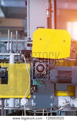 Factory machine with yellow panels. Device with small motor. Motor supplying energy to conveyor. Morning at industrial workshop.