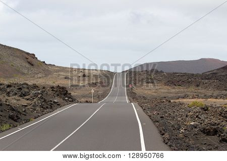 Highway road with wihite centre line in Timanfaya, Lanzarote. Spain. Road to volcano