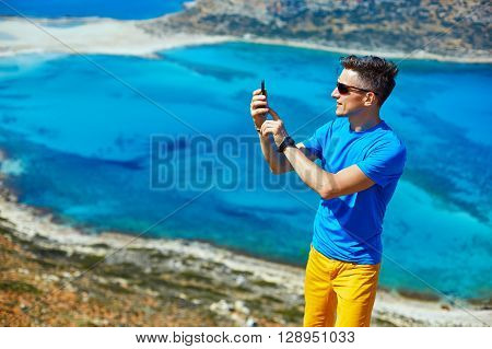 man  traveler   standing on the cliff against sea and blue sky at early morning. Balos beach on background, Crete, Greecee. man taking a photo on smartphone
