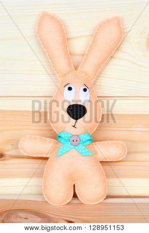 Beige Easter felt rabbit on a natural wooden Board
