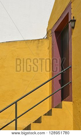 Yellow steps leading up to red doorway in Funchal Madeira Portugal