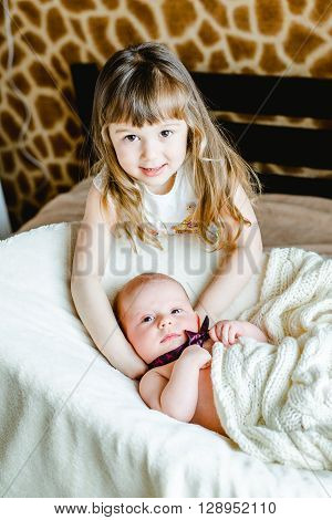 Little sister hugging her newborn brother. Toddler kid meeting new sibling. Cute girl and new born baby boy relax in a white bedroom. Family with children at home. Love trust and tenderness concept.