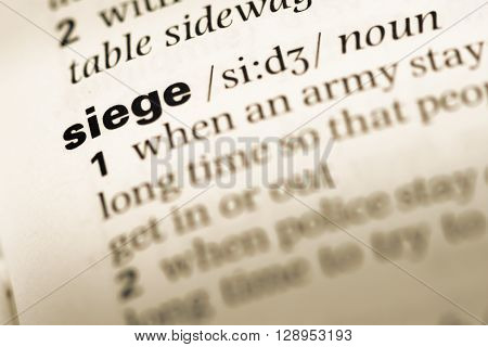Close Up Of Old English Dictionary Page With Word Siege.