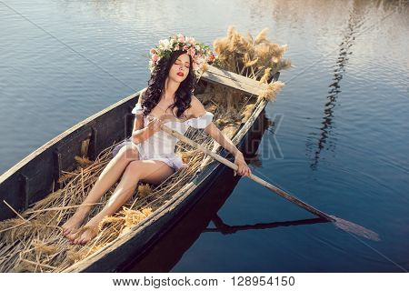 Young sexy woman sailing on boat at sunset. The girl has a flower wreath on her head, relaxing and seiling on river. Fantasy art photography. Concept of female beauty, rest in the nature, and travel by water