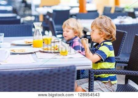 Two little kid boys having healthy breakfast in hotel restaurant or city cafe. Funny children eating vegetables and drinking juice Selective focus.