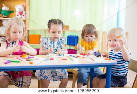 kids group learning arts and crafts in playroom with interest