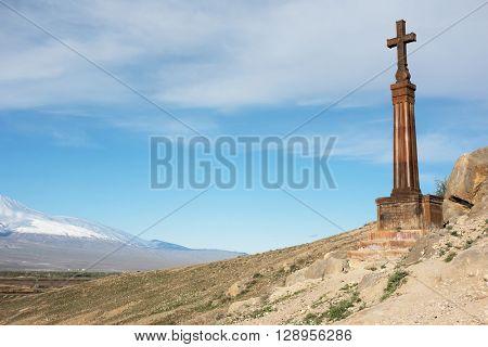 Christian cross in ancient monastery Khor Virap near Turkish-Armenian border in front of Ararat mountain