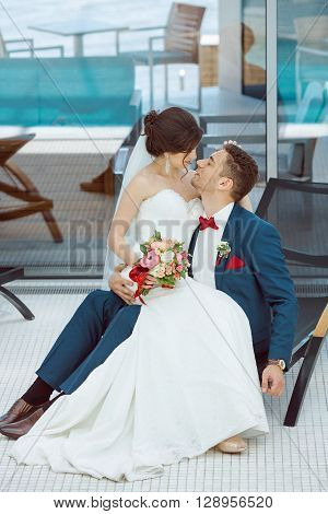 Wedding couple in love. Beautiful bride in white dress and veil and brides bouquet with handsome groom in blue suit sitting on plank bed and embracing each other indoors at pool. Full lenght portrait of man and girl. Concept of wedding celebration in vaca