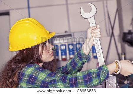 Portrait Of Young Female Metalworker Engaged With Wrench