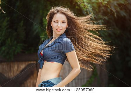 Beautiful happy young girl in jeans overalls with a hairdress gafra posing in park. Fashion portrait of sexy model