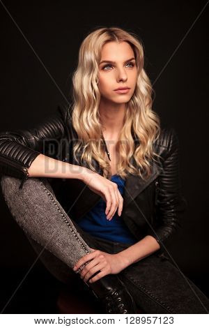 side view portrait of a blond woman in leather jacket sitting and looking away from the camera
