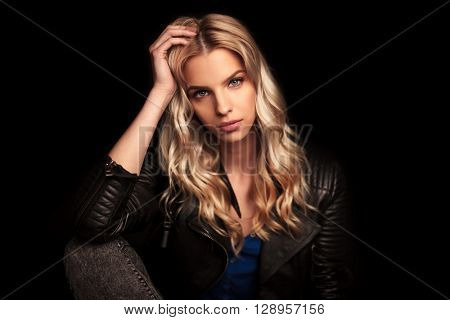 young woman in leather jacket resting her head on her palm and looks at the camera