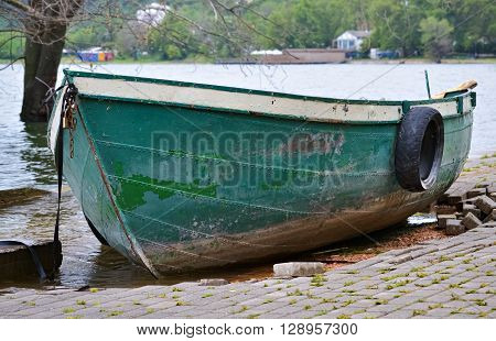 Closeup of a small green rowboat on the shore of the lake