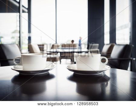 Coffee cups on table with blurred people in Restaurant lounge cafe Interior seats