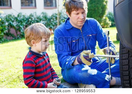 Little blond kid boy and his father changing wheels on car with pneumatic wrench. Man in uniform teaching his son working with tools.
