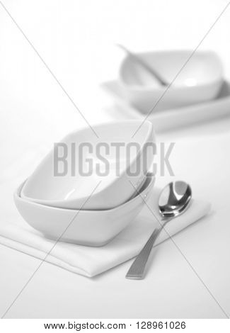 Empty and unused white crockery. Bowls and spoon on white background.