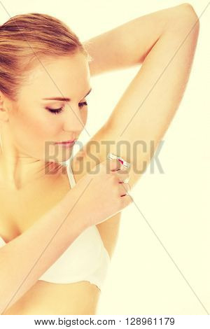 Young woman shaving armpit pink razor