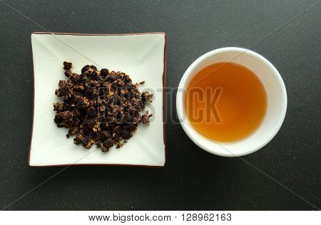 Chinese herbal tea with a cup full of tea. View from above.