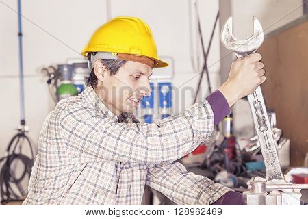 portrait of young metalworker engaged with wrench