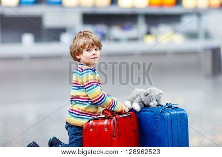 Beautiful little kid boy with blue and red suitcases and toy on international airport. Happy child waiting for flight and going on vacations.