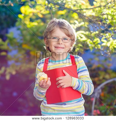 Adorable little kid boy with glasses, books, apple and backpack on his first day to school or nursery. Child outdoors on warm sunny day, Back to school concept