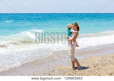 Young mother and little toddler boy having fun on beach of ocean. woman and kid son hugging. Carefree childhood and happy parenting.