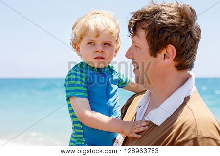 Young father and little toddler boy having fun on beach of ocean. man and kid son hugging. Carefree childhood and happy parenting.