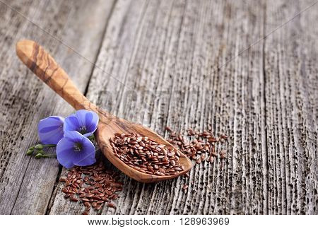 Flax seeds with flowers in a wooden board