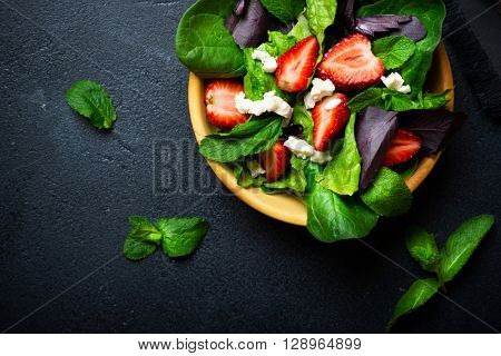 Healthy vegetable salad with strawberry and cheese in wooden bowl on a dark background