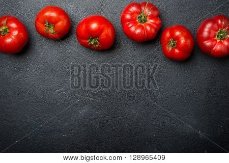 Ripe red tomatoes on a dark stone background, top view