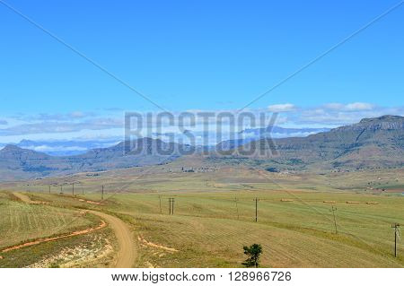 Drakensberg mountains with grass, trails and blue sky background
