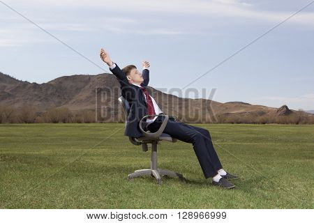 Businessman sitting on chair on green meadow on blue sky background