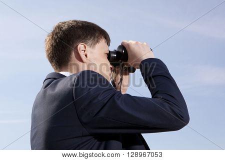 Business concept. Businessman looks through a binoculars
