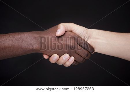 African man's hand shaking white man's hand on black background