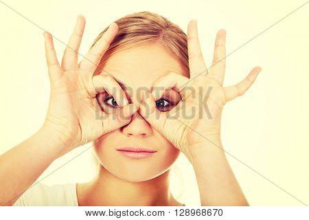 Young woman making binoculars hands