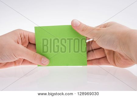 Hand holding a light green color rectangular paper on a white background